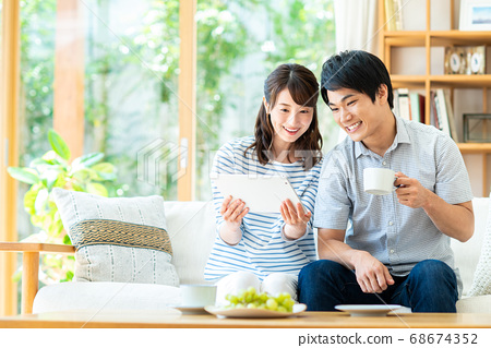 Young couple using a tablet in the living room 68674352