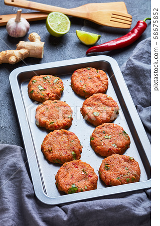 raw thai fish cakes on a baking sheet 68675852