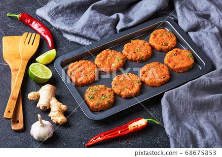 raw thai fish cakes on a baking sheet 68675853