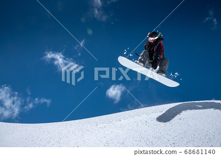A professional snowboarder girl in flight after jumping from a snow eaves makes a rake against blue sky in sunny day. The concept of winter sports freeride and freestyle 68681140