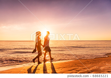 Couple walking on beach at sunset silhouettes - Romantic summer travel holidays in Caribbean destination 68683221