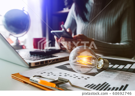 light bulb with business hand working with tablet, laptop computer and creative business strategy in morning light 68692746