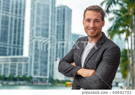 Happy smiling young caucasian businessman man confident with crossed arms portrait wearing smart casual professional blazer on urban city background cityscape 68692782