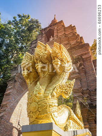 Gold Three Head Serpent or Naga Statue on Pagoda Brick Door Background in Portrait View 68696253