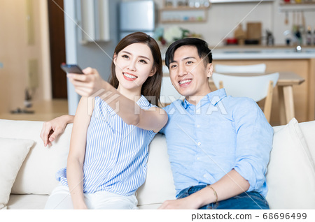 couple watch tv at home 68696499