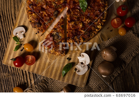 Fresh baked italian pizza with ingredients on old rustic wood table 68697016