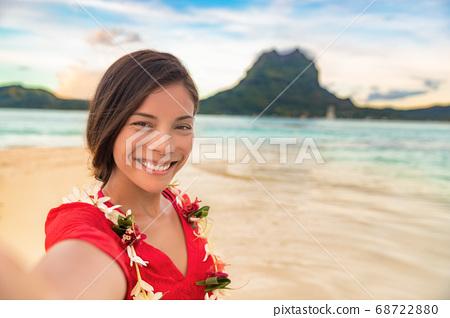 Luxury vacation selfie happy woman smiling taking photo with mobile phone on Bora bora island cruise travel destination at sunset. Smiling gorgeous Asian girl wearing Tahiti flower lei for luau 68722880