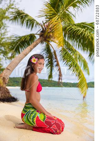 Beach woman relaxing on Bora Bora Tahiti island under the sun wearing polynesian skirt and monoi flower with palm tree background. Polynesia culture travel concept 68722883