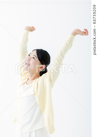 Smiling young woman raising both hands 68739209