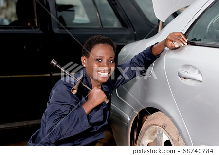 Young smiling mechanic crouched near the tire of a 68740784