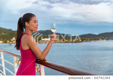 Luxury cruise ship vacation elegant woman drinking glass of champagne at dinner enjoying ocean view from boat. Asian lady in red dress relaxing on deck outdoor 68742264
