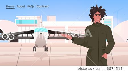 man pilot in uniform standing near plane airport terminal aviation concept portrait horizontal 68745154
