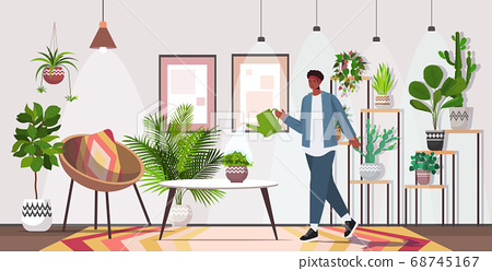 man with watering can taking care of houseplants living room or home garden interior 68745167