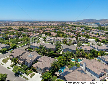 Aerial view of suburban neighborhood with big mansions with pool in San Diego 68745576