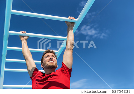 Fitness monkey bars man training arms muscles on jungle gym outdoors in summer. Athlete working out gripping climbing on ladder equipment at sport athletics centre 68754835