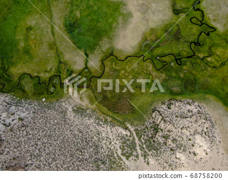 Aerial view of green land and small curve river with mountain in the background in Aspen Springs 68758200