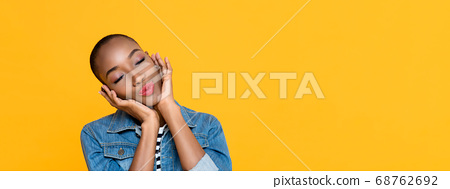 Panoramic portrait of young African American woman daydreaming while touching her face  68762692