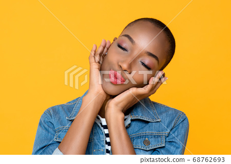 Portrait of young African American woman daydreaming while touching her face  68762693