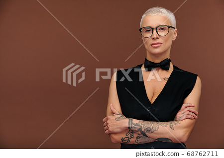 Masculine blond female in black waistcoat and bowtie crossing her arms on chest 68762711