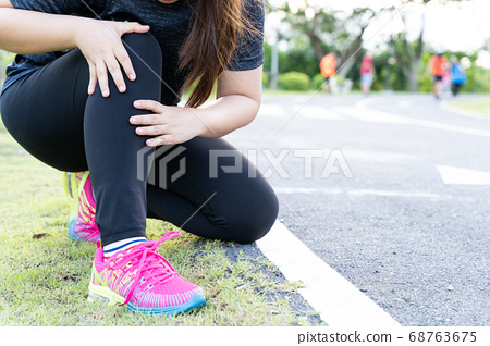 Asian woman use hands hold on her knee injury 68763675