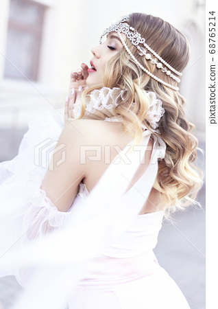 Fashionable blonde in a vintage dress with a luxurious decoration on her head. Street shooting in the daytime. 68765214