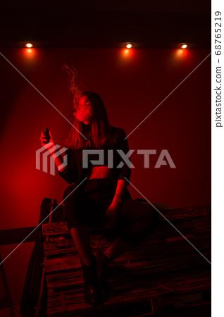 Girl model smokes vape in red light. 68765219
