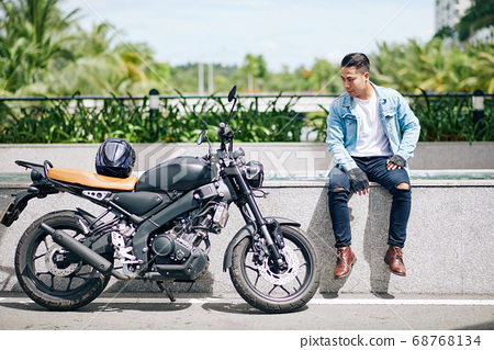 Proud man looking at motorcycle 68768134