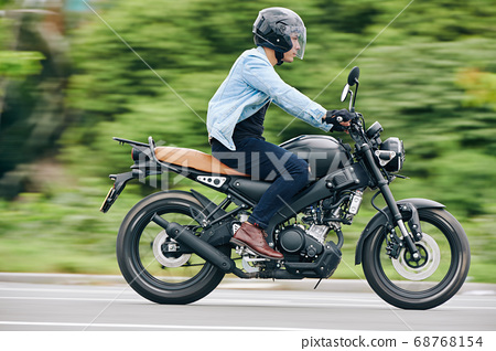 Riding fast on motorcycle 68768154