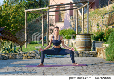 Young woman doing a Goddess squat yoga pose 68769600