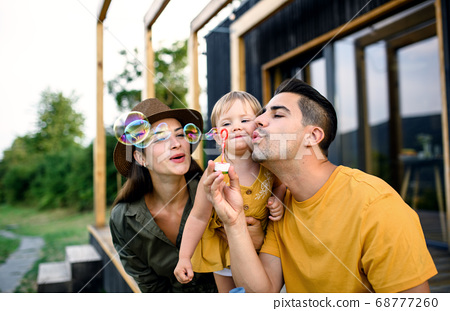 Young family with small daughter outdoors, weekend away in container house in countryside. 68777260