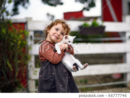 Small girl with cat standing on farm, looking at camera. 68777746
