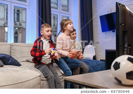 Funny three child friends are sitting on the couch at home and enjoying soccer match and shouting when see scored ball. 68780846