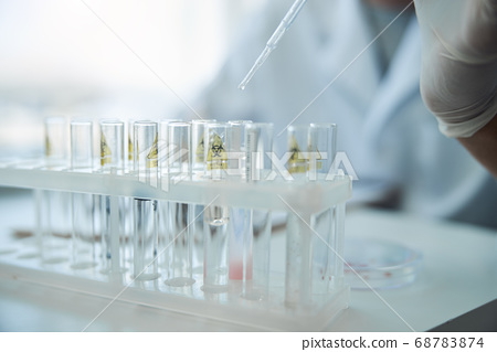 Caucasian scientist taking a sample of liquid 68783874