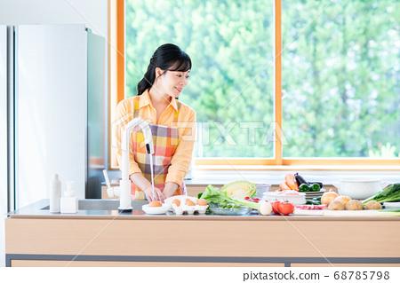 주방에서 요리를하는 중간 여성 68785798