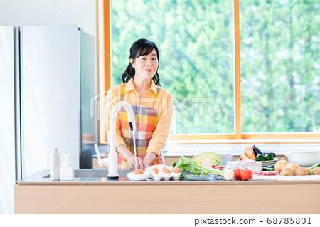 주방에서 요리를하는 중간 여성 68785801