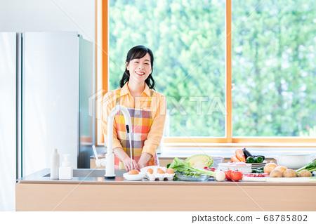 주방에서 요리를하는 중간 여성 68785802
