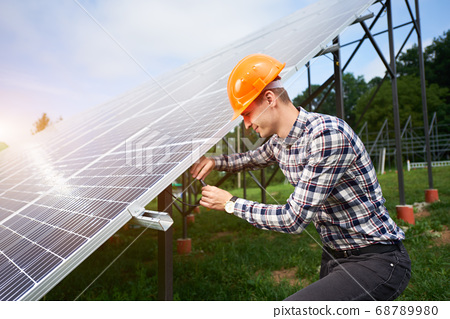 Worker connects solar panels on a green plantation. Home construction. 68789980
