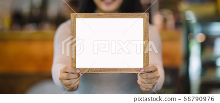 woman holding blank wooden frame in coffee shop 68790976