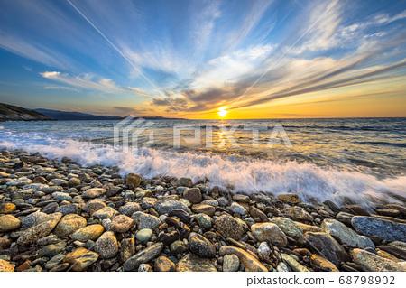 Waves breaking on pebble beach 68798902