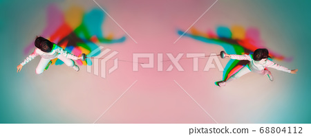 Teen girl in fencing costume with sword in hand on gradient background with neon light, top view 68804112