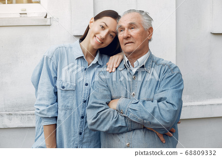Old man standing on gray backround with his granddaughter 68809332