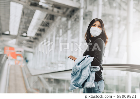 woman tourist wearing face mask holding passport 68809821