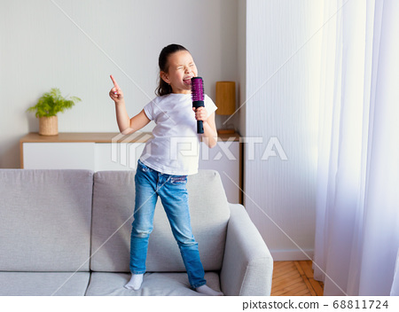 Chinese Little Girl Singing Holding Hairbrush Like Microphone At Home 68811724