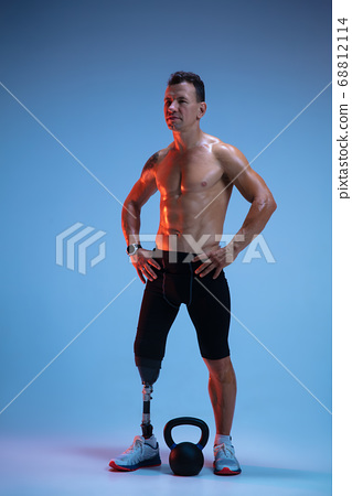 Athlete with disabilities or amputee isolated on blue studio background. Professional male sportsman with leg prosthesis training with weights in neon 68812114