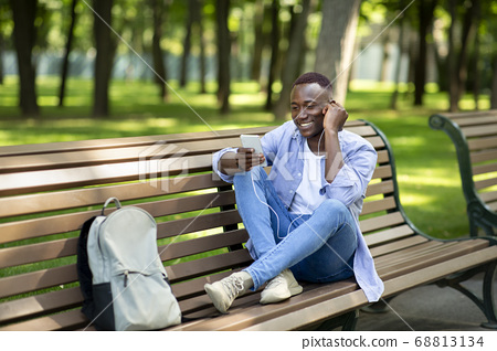 Funky African American guy sitting on bench and enjoying music on mobile phone at park, free space 68813134