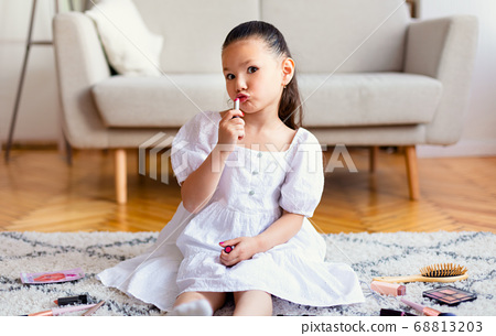 Little Girl Putting On Lipstick Playing With Mother's Cosmetics Indoor 68813203