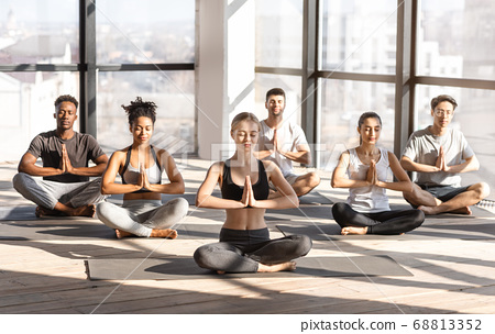 Yoga Session. Young multicultural people doing group meditation in modern studio 68813352