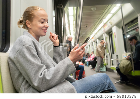 Portrait of lovely girl typing message on mobile phone in almost empty public subway train. Staying at home and social distancing recomented due to corona virus pandemic outbreak 68813578