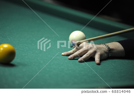 Playing billiard. Player arm gets ready to stroke a ball with a cue 68814046