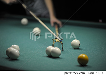 Billiard player striking a ball with cue stick 68814624